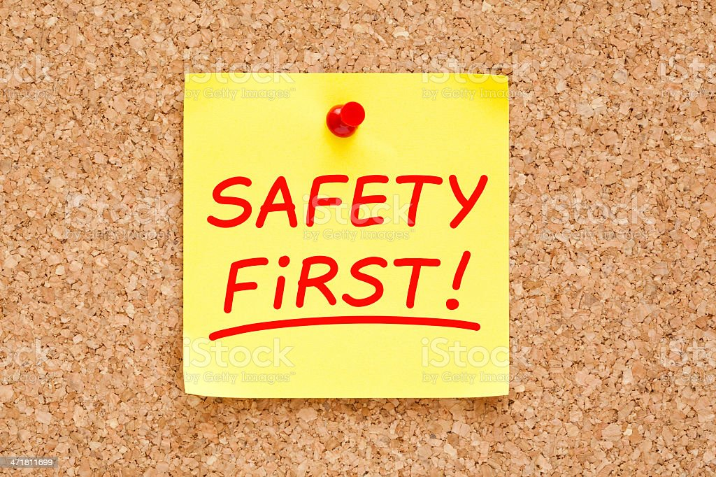 A sticky note on a cork-board saying safety first! stock photo