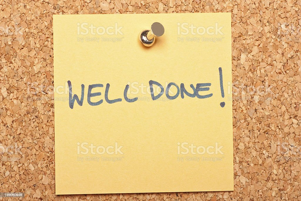 Sticky note with push pin in cork board reading Well done  royalty-free stock photo
