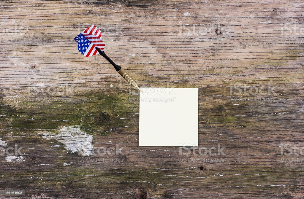 Sticky notes with darts on wooden background stock photo