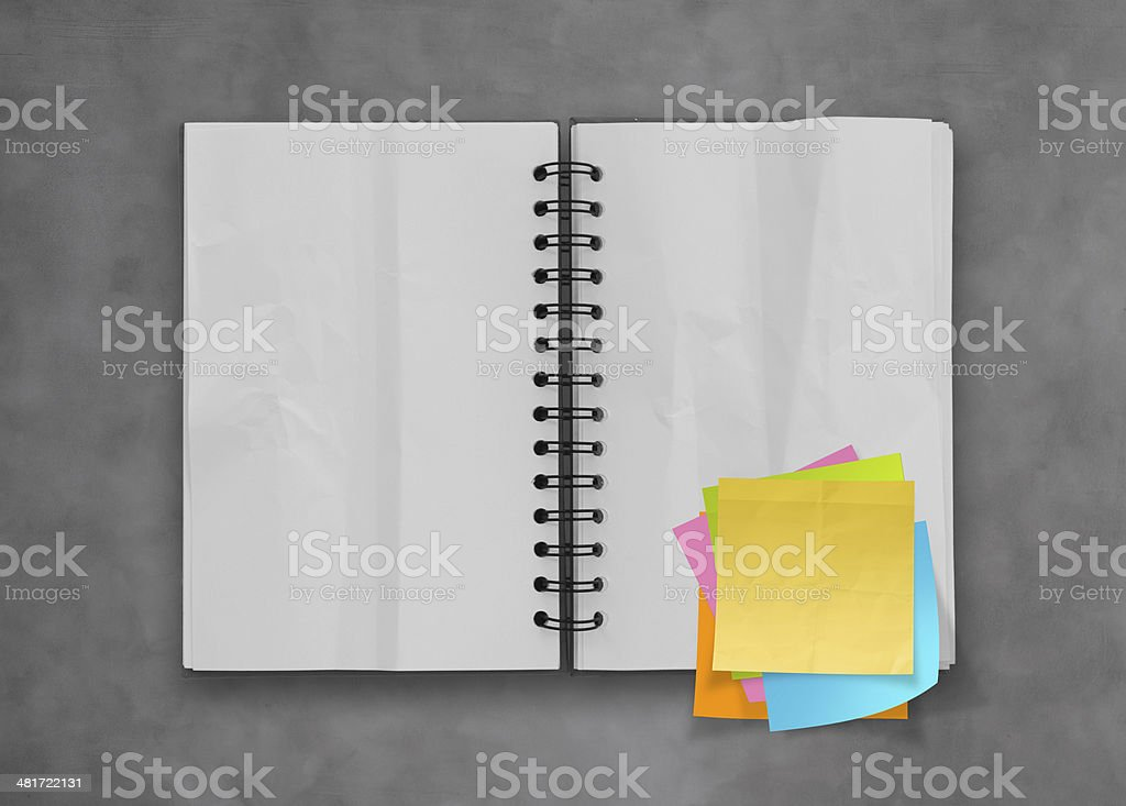 sticky notes with open blank note book on desk top texture