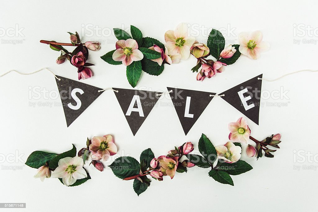 Still life arrangement of flowers and pennant text of sale stock photo