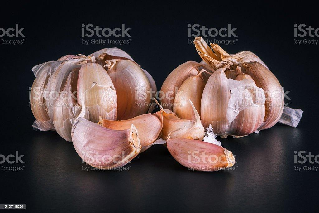 still life arrangement of Three whole garlic bulbs grouped stock photo