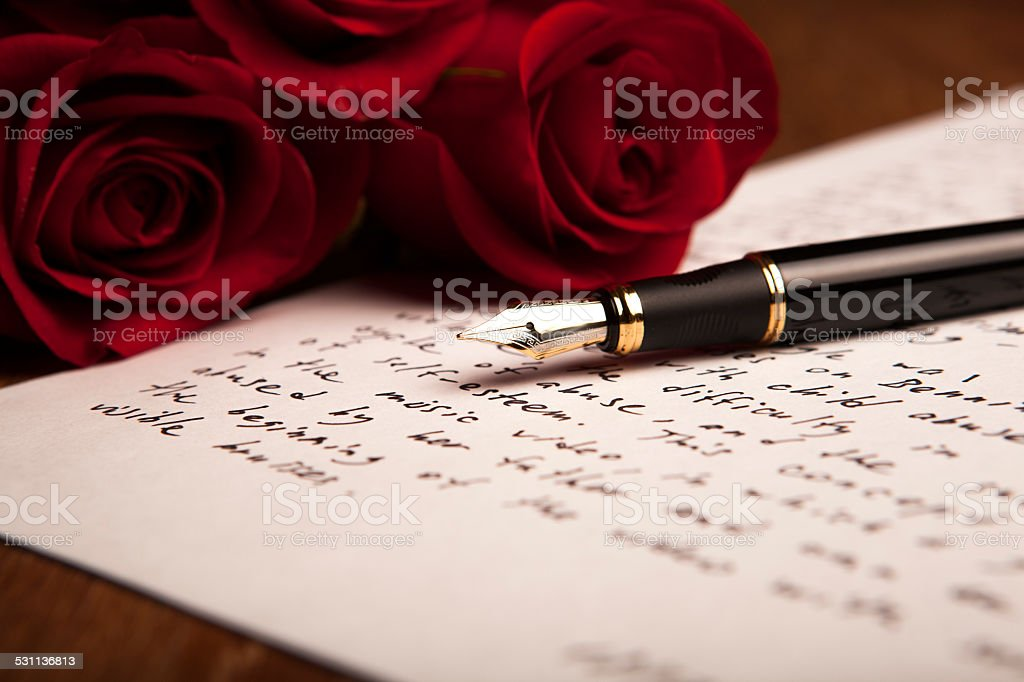 still life of a fountain pen, paper and flowers roses stock photo