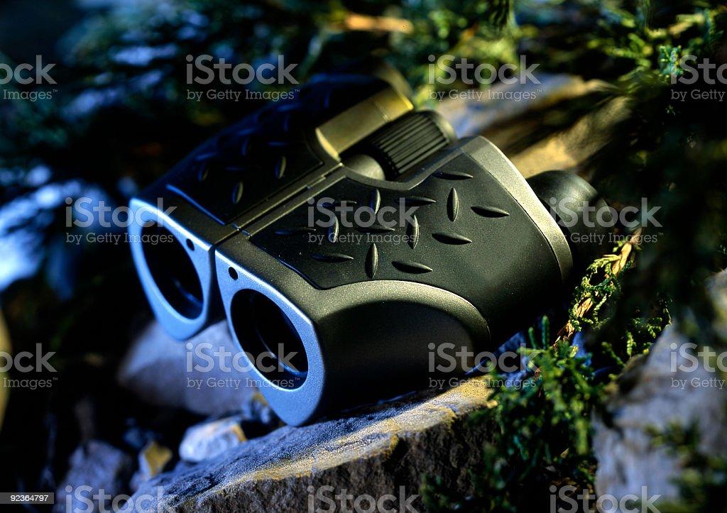 Still life of binoculars on rocks stock photo