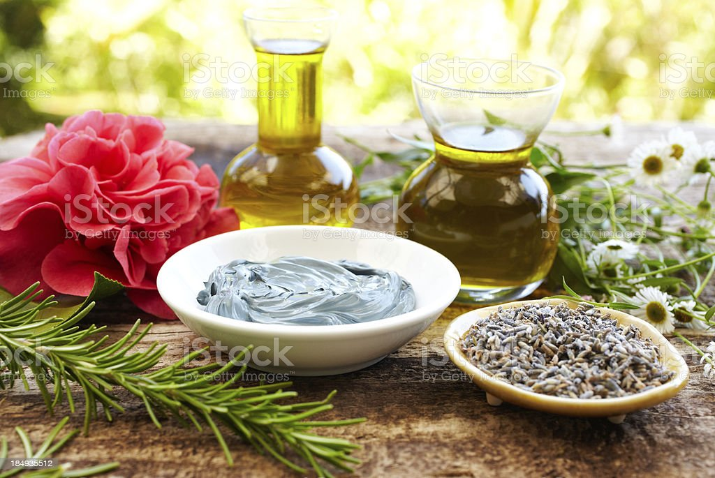 Still life of herbs, massage oil, mud mask, rosemary, flowers stock photo