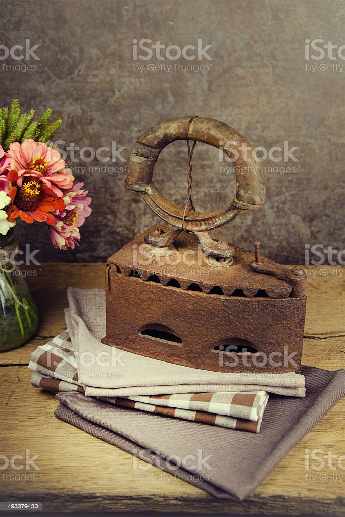Still life of old iron and flowers on vintage background. stock photo