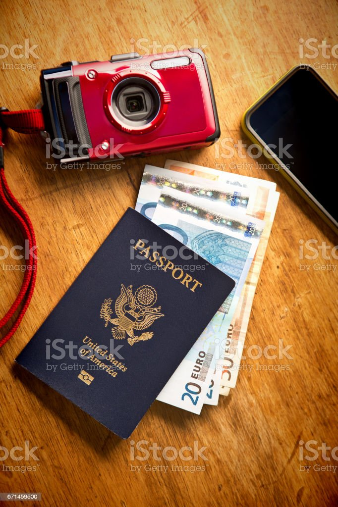 Still Life of Travel Essentials Passport, Euros Currency, Camera and Phone stock photo