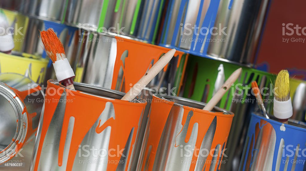 Still life of Used multi colored paint cans with paintbrushes royalty-free stock photo