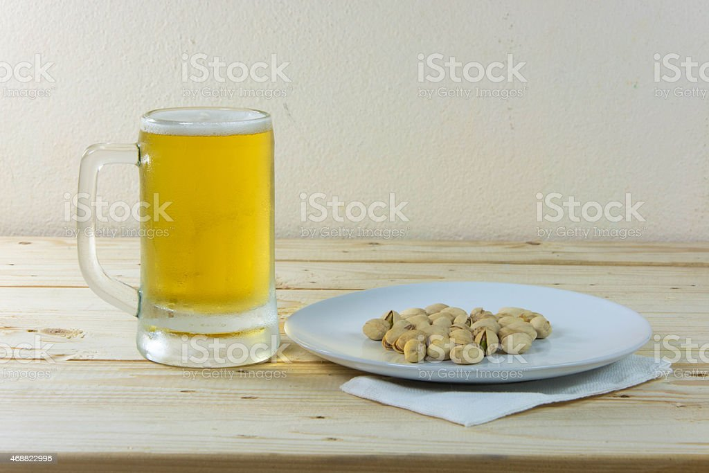 Still life pistachios and beer in glass on wooden table stock photo