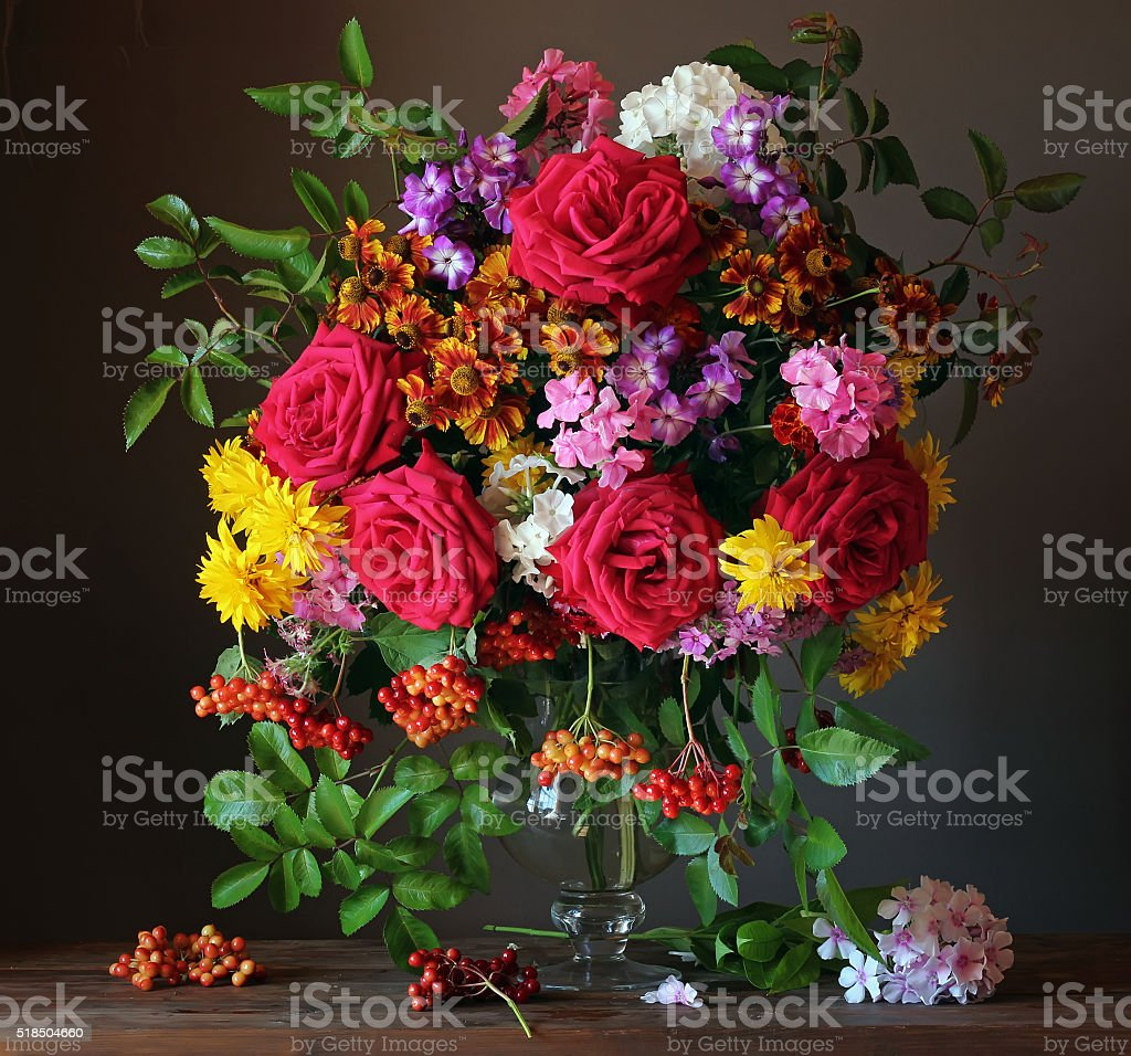Still life with a bouquet of garden flowers and berries. stock photo