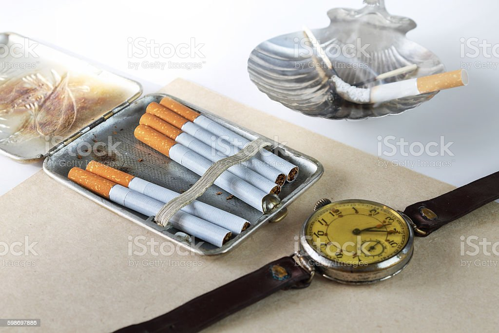 Still life with a cigarette case and hours stock photo
