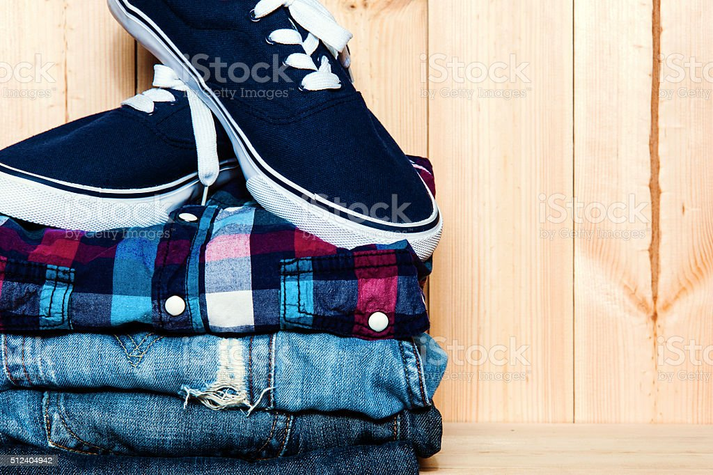 still life with  blue sneakers, shirt and jeans on wooden stock photo