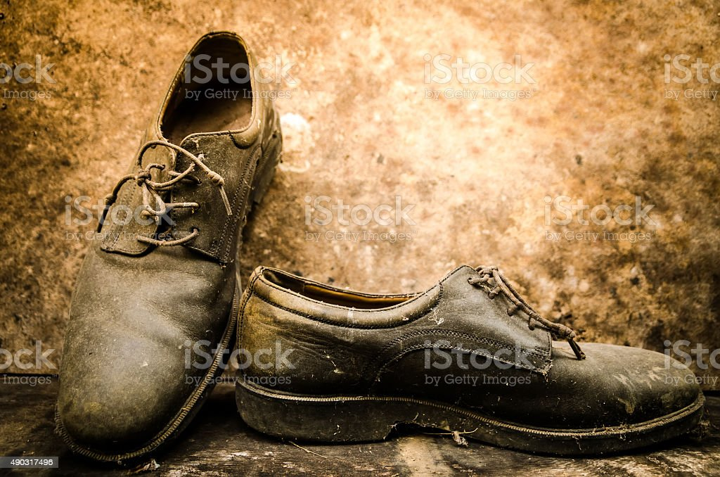 still life with boots on wooden table over grunge background stock photo