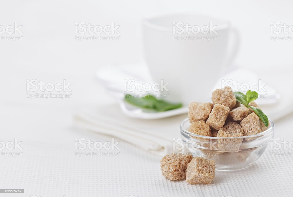 Still life with brown lump cane sugar, on white linen royalty-free stock photo
