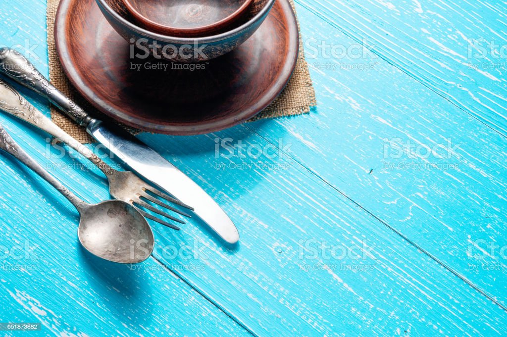 Still life with brown rustic ceramic plate and old cutlery set on blue wooden table with copy space stock photo