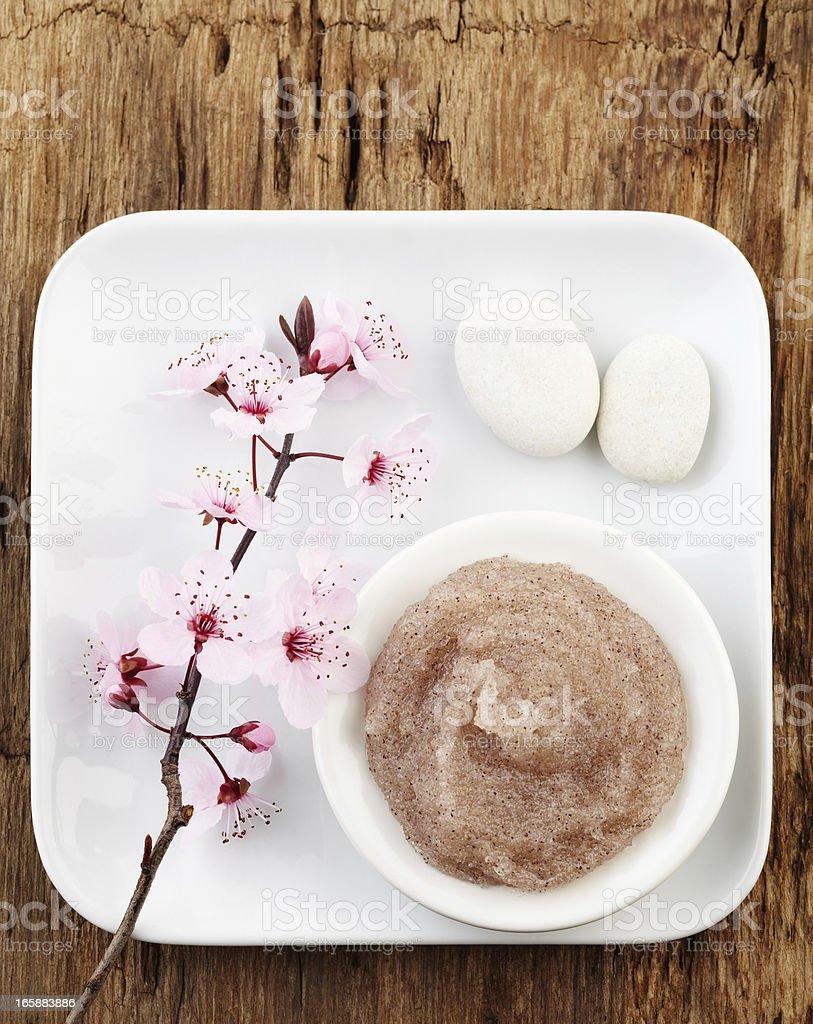 Still life with cherry blossom, salt scrub and white pebbles stock photo