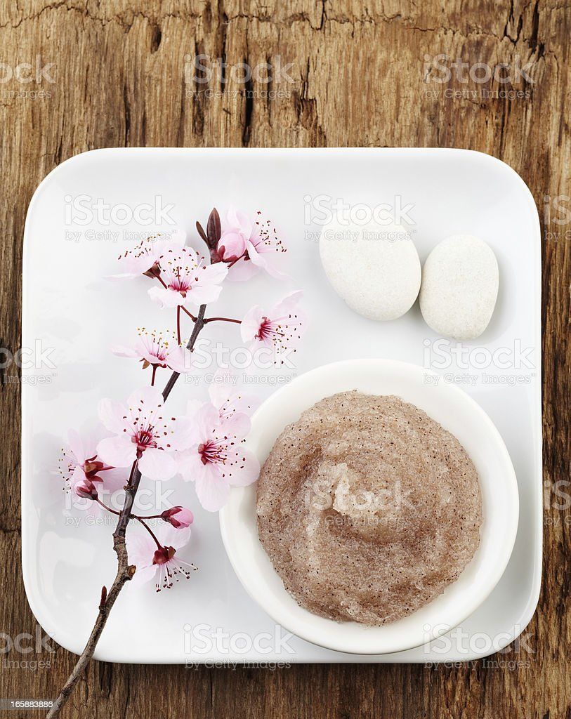 Still life with cherry blossom, salt scrub and white pebbles stock photo