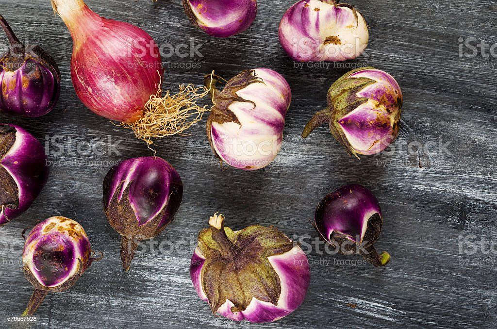 still life with eggplants and onion  on a wooden table stock photo