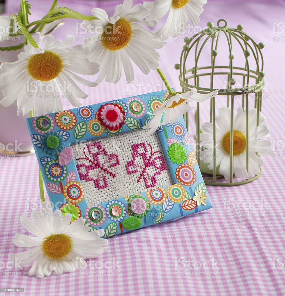 Still life with embroidered cross-stitch butterflies and camomiles royalty-free stock photo