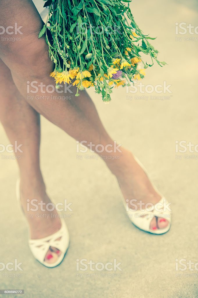 Still life with female legs and flower bouquet stock photo