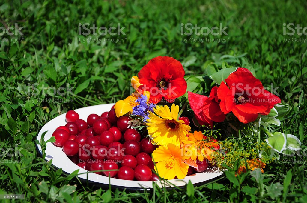 Still life with flowers and cherry on plate stock photo