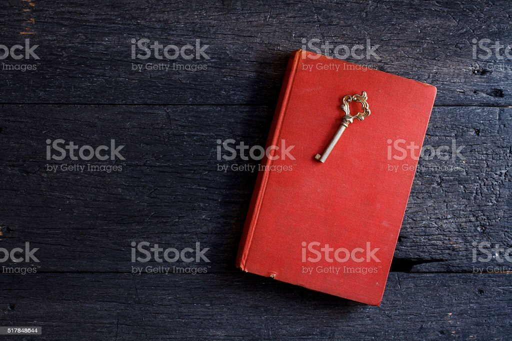 Still life with old book and key on wooden stock photo