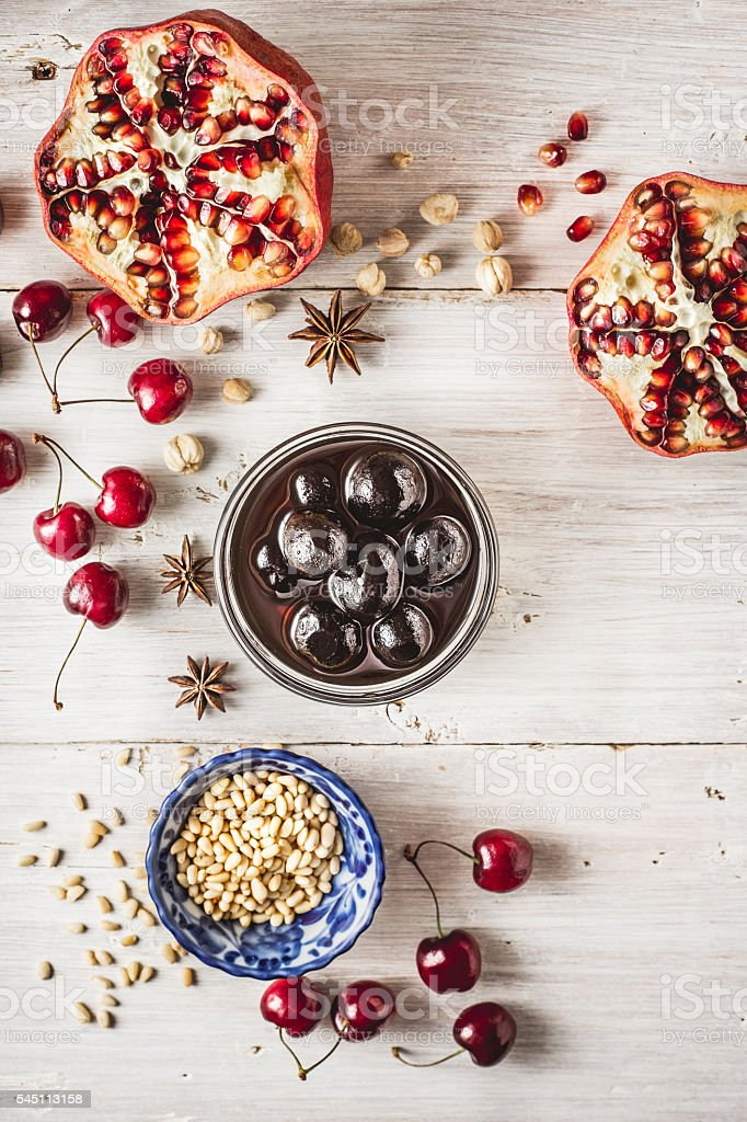 Still life with pomegranate , cherry and spices on white  table. stock photo