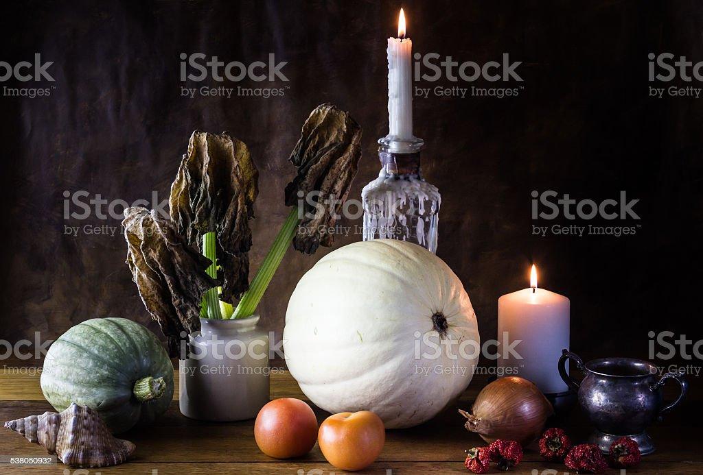 Still life with pumpkin, dead pumpkin leaves, candles, earthenwa stock photo