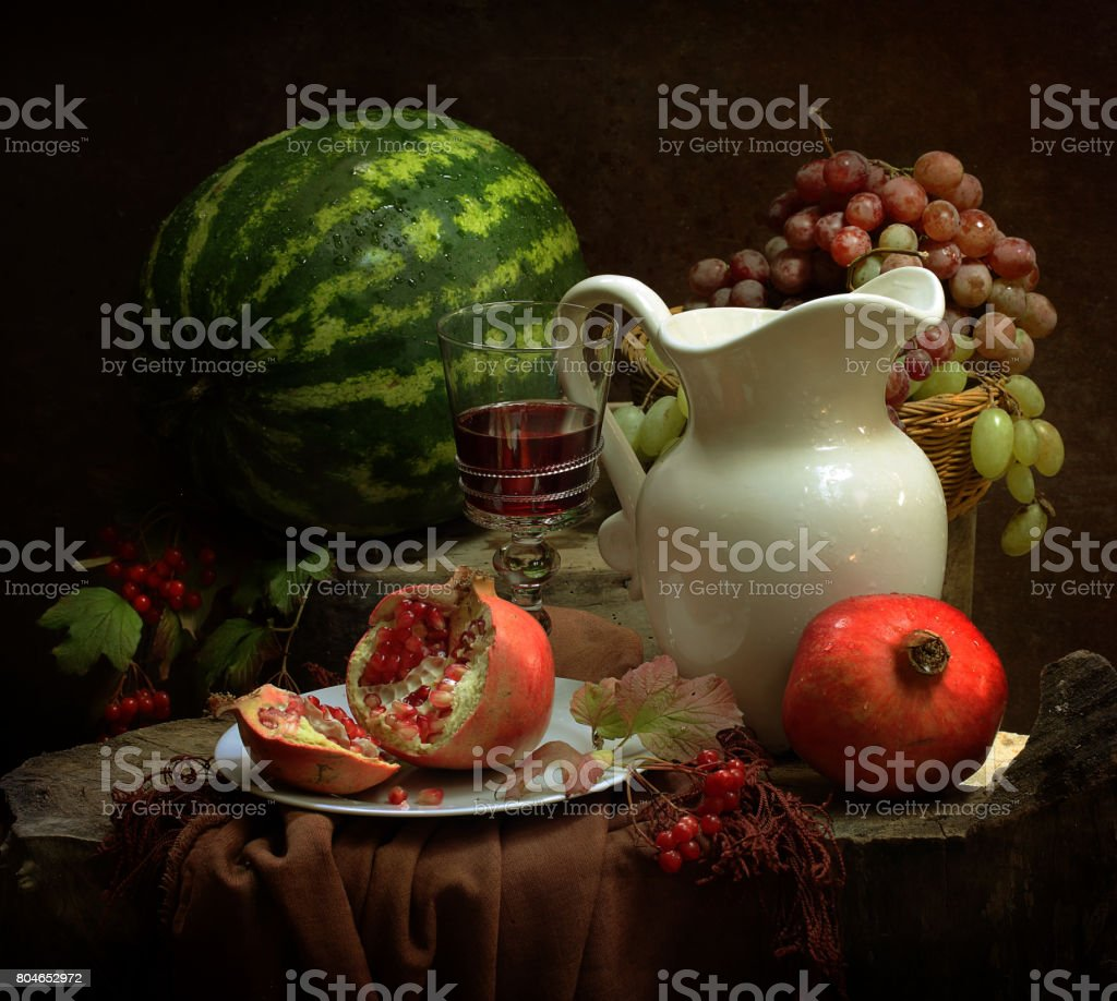 Still life with red wine, figs, grapes and watermelon stock photo