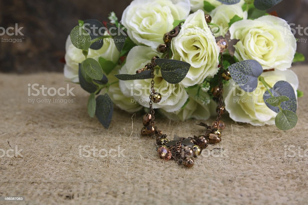 Still life with rose flower and bronze nacklace on sackcloth stock photo