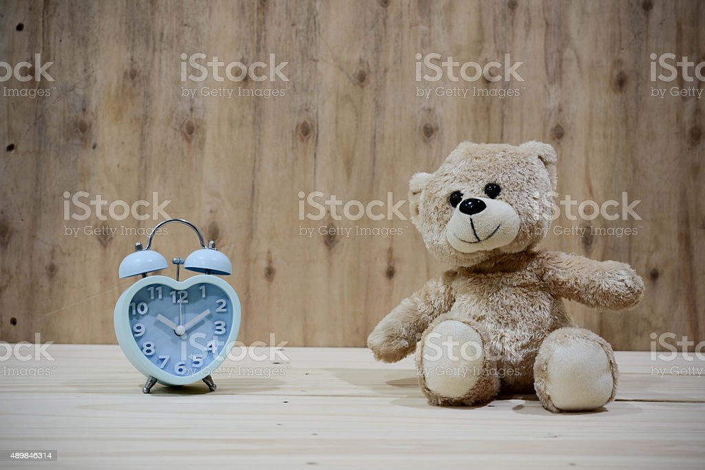 Still life with teddy Bear with clock on wood background stock photo