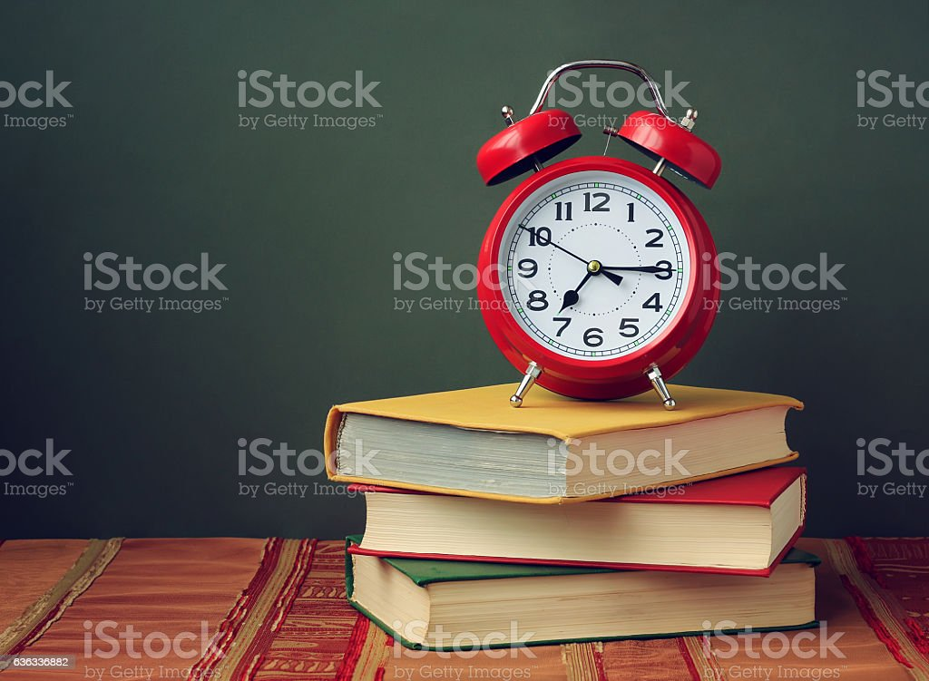 Still life with three books and a red alarm clock. stock photo