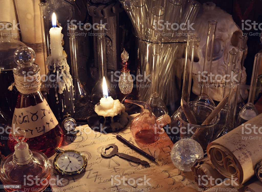 Still life with vintage bottles, magic objects and paper scrolls stock photo