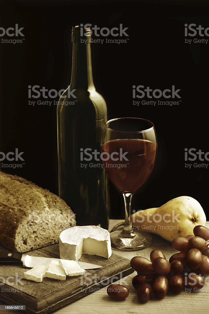 Still life with wine cheese and fruit. Hand coloured sepia. stock photo