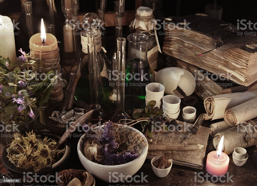 Still life with witch books, scrolls, herbs and magic objects stock photo