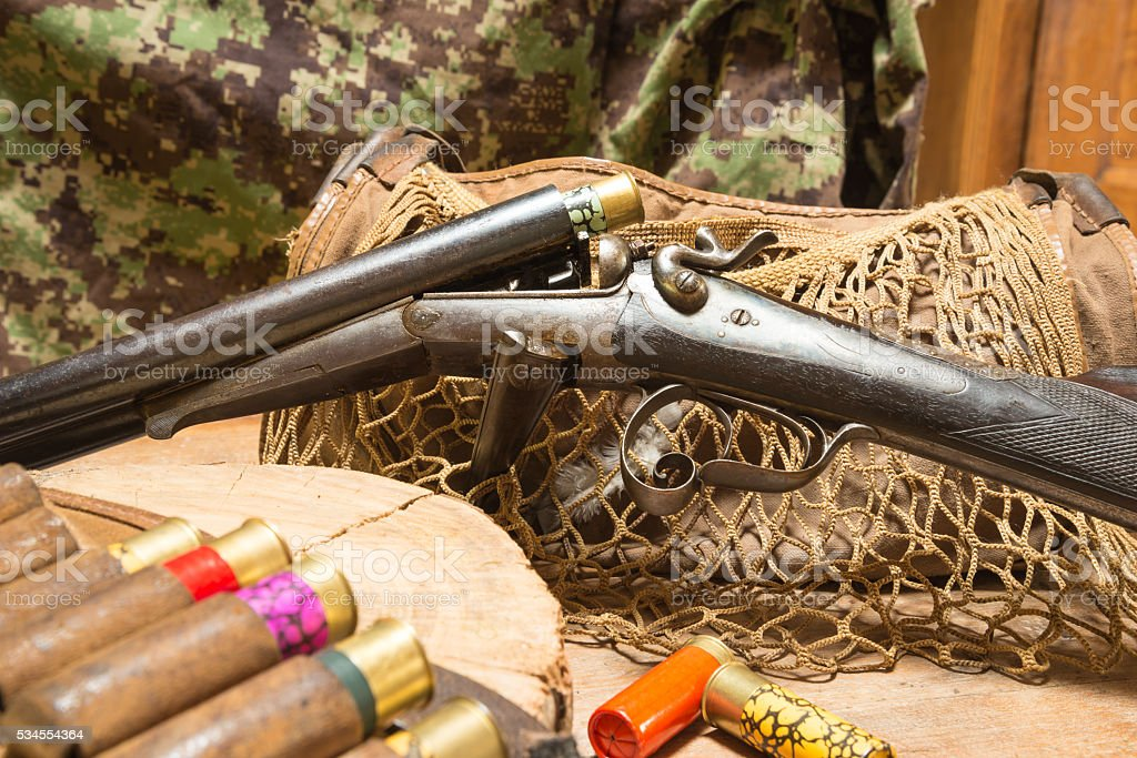 Still life.Vintage shutgun and hunting ammunition on a wooden background stock photo