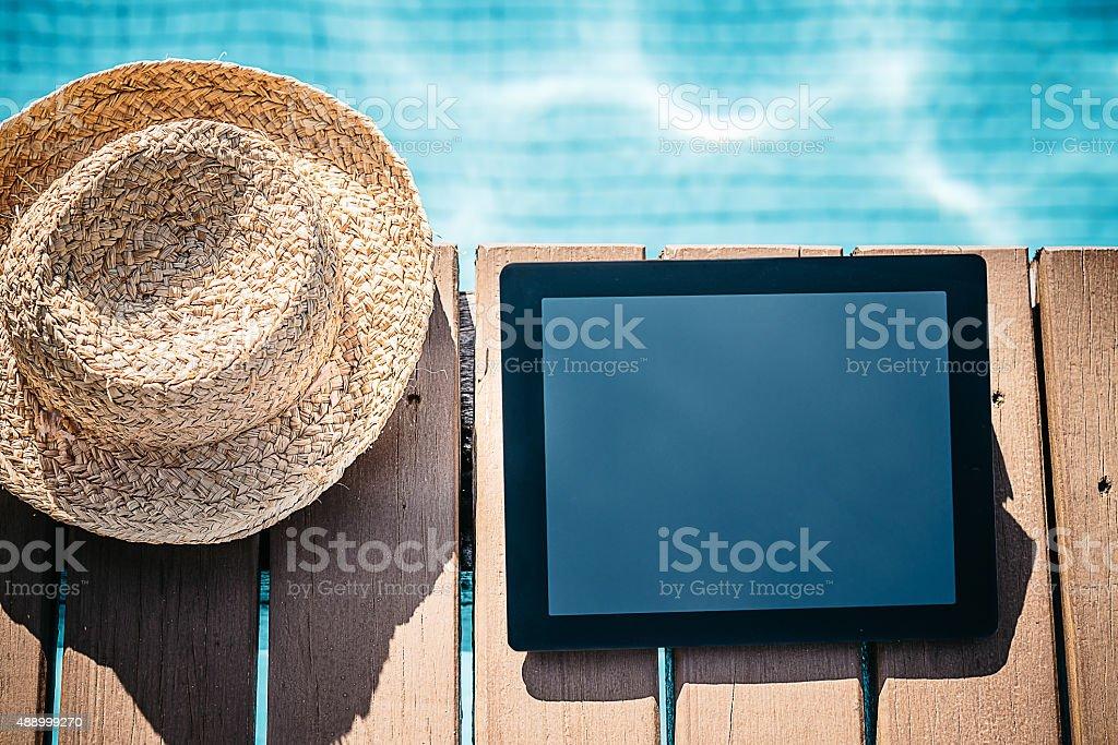 still of digital tablet beside sun hat at swimming pool stock photo