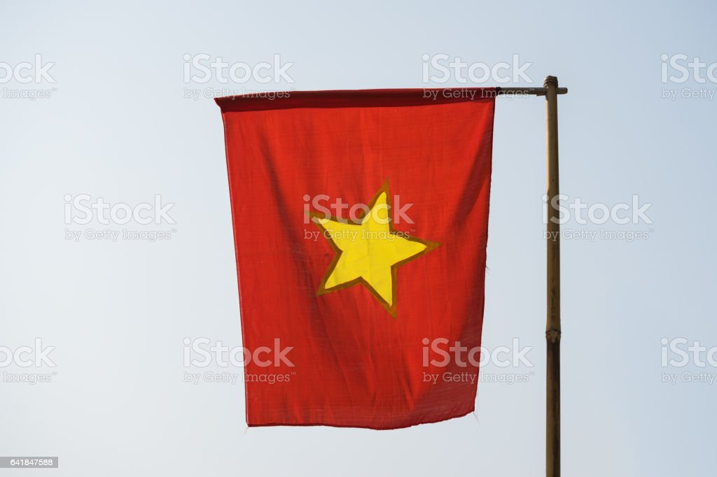 Still Vietnamese flag on wooden flagpole made of bamboo dry tree, in foggy morning stock photo