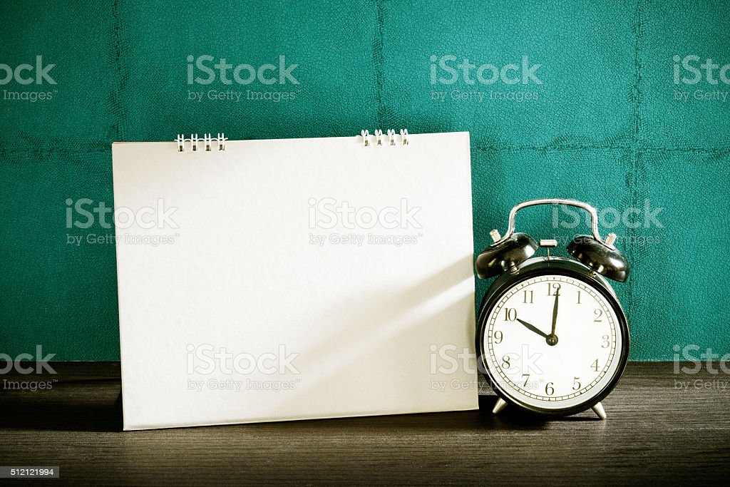 Stillife of desk calendar with alarm clock on wood table. stock photo