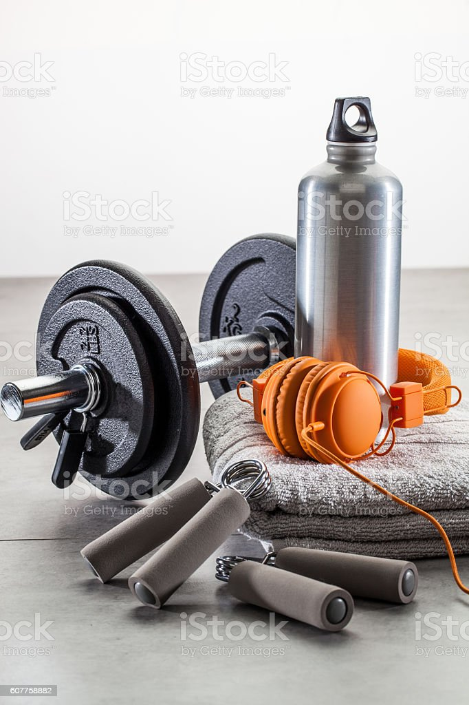 still-life of dumbbells, hand grip with fashionable earphones stock photo