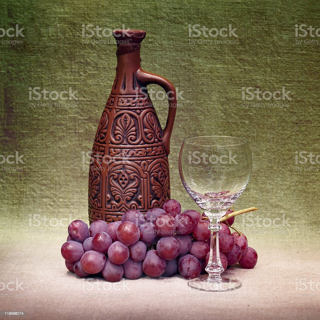 Still-life with clay bottle, glass and grapes against canvas royalty-free stock photo