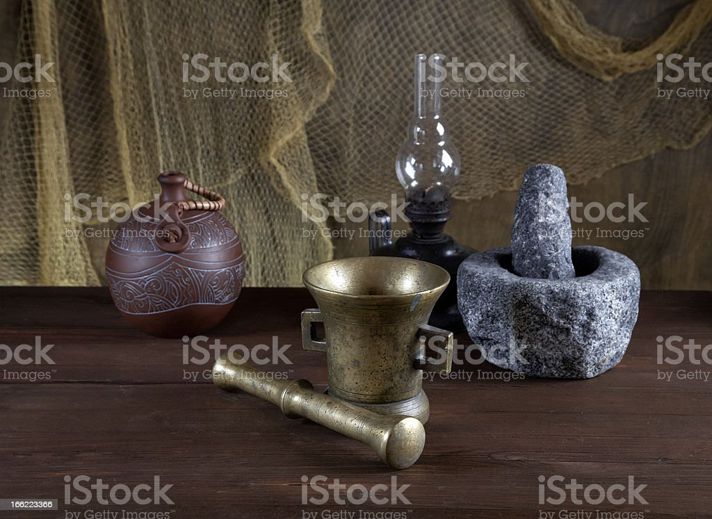 Still-life with mortars and an oil lamp on  old table royalty-free stock photo