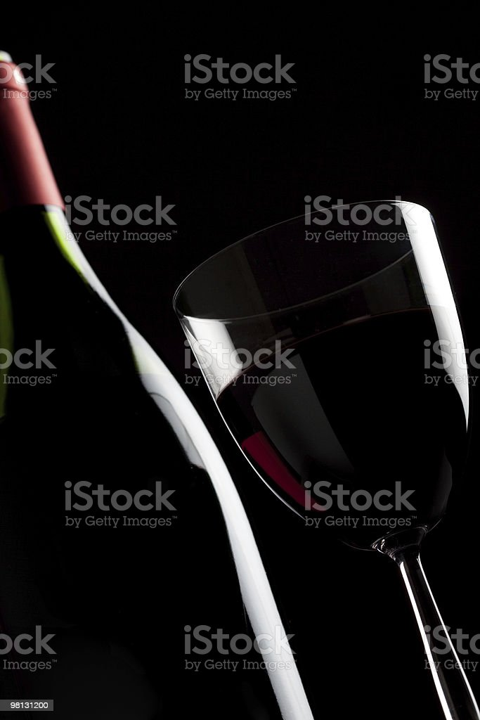 Still-life with one wine bottle and glass over black background royalty-free stock photo