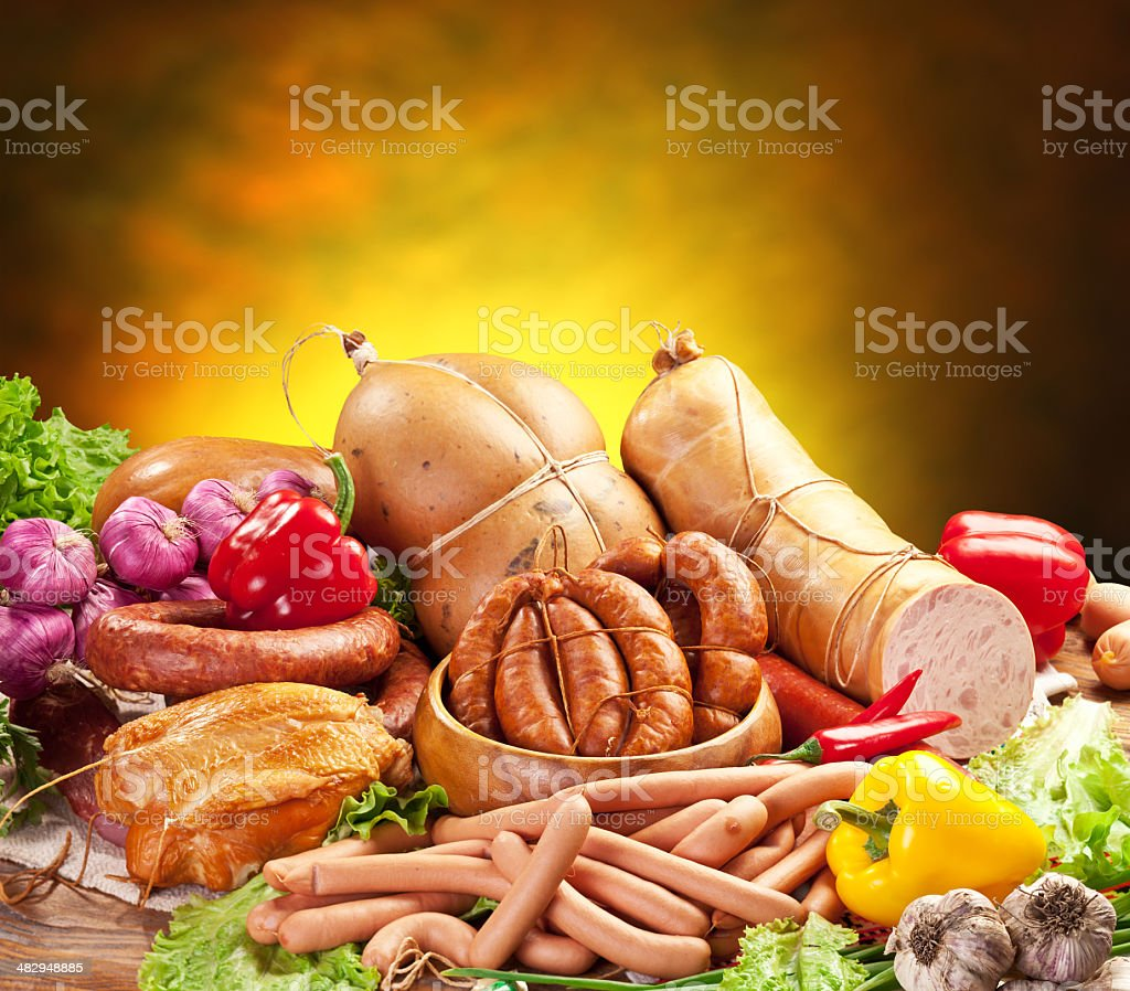 Still-life with sausage products, vegetables and herbs. stock photo