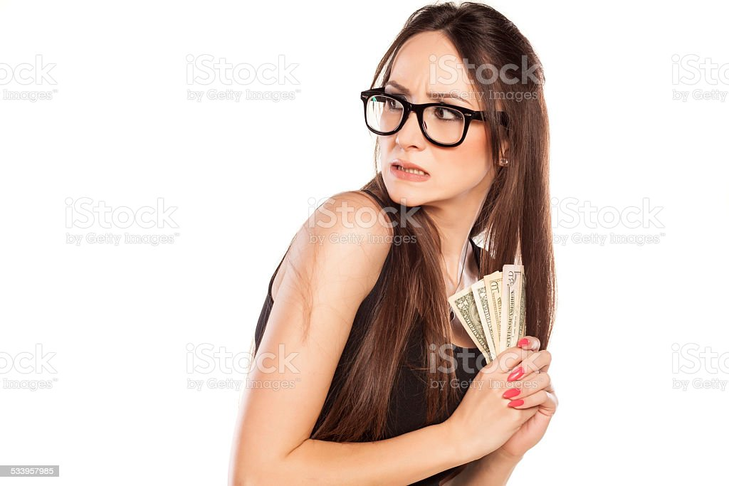 Stingy beautiful woman holding her money stock photo