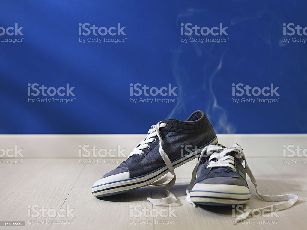 stinking worn-out shoes left on wooden floor stock photo