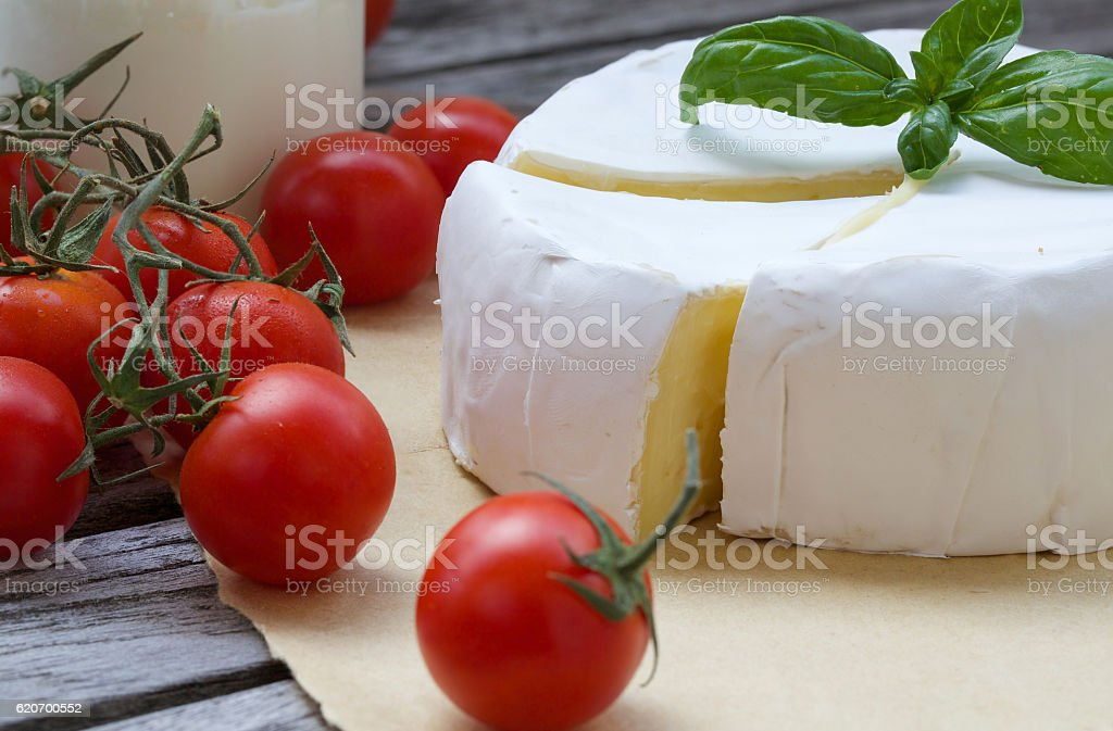 Stinky French cheese and red cherry tomatoes. Closeup stock photo