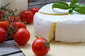 Stinky French cheese and red cherry tomatoes. Closeup