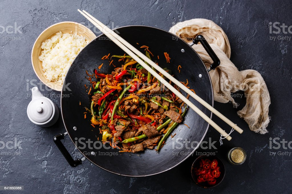 Stir fry beef meat with vegetables and rice in wok pan stock photo