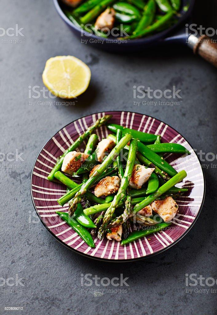 Stir-fired sesame chicken, green asparagus and sugar snap peas stock photo